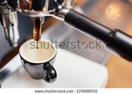 High angle shot of a drop of fresh coffee falling from the spout of a coffee machine espresso dispenser into a clean ceramic cup - stock photo