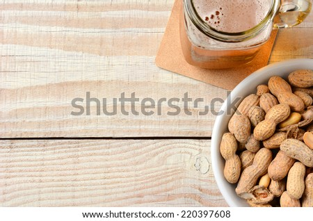 High angle shot of a glass of beer and a bowl of peanuts on a white wood table. Horizontal format with copy space. - stock photo