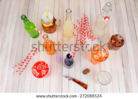 High angle shot of a group of assorted summer drinks. Lemonade, ice tea, soda, cola, orange soda and strawberry soda on a rustic wood table.  - stock photo