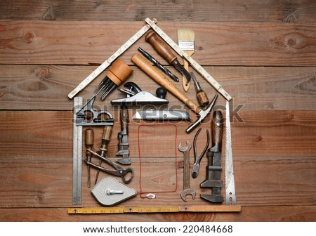 High angle shot of a group of construction tools arranged in the shape of a house. Horizontal format on a rustic wood background. - stock photo