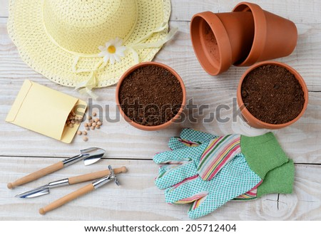 High angle shot of a group of items for potting and planting seeds. Horizontal format on a rustic wooden potting table. Items include, shovel, hat, flower pots, soil, gloves, seed packet and more.  - stock photo