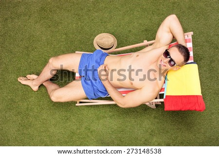High angle shot of a handsome shirtless man with sunglasses sunbathing in a sun lounger in his backyard, and looking at the camera - stock photo