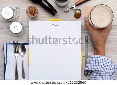 High angle shot of a man holding his glass of beer on a restaurant table with a blank menu in front of him. Only the man's hand and arm are visible. - stock photo