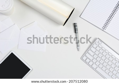 High angle shot of a neat white desk with primarily white office objects. Items include, a tablet computer, keyboard, pad, pen, coffee cup, and envelopes. With copy space. - stock photo