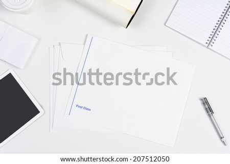 High angle shot of a neat white desk with primarily white office objects. Items include, tablet computer, pad, pens, coffee cup, and envelopes. - stock photo
