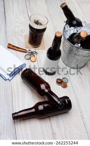High angle shot of a party bucket filled with beer bottles on a rustic wood table. Empty bottles and bottle caps are on the table along with a glass of dark ale and bar towel. - stock photo