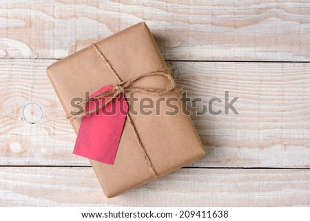 High angle shot of a plain brown paper wrapped Christmas present on a whitewashed wood table. The gift is tied with twine with a blank red gift tag. - stock photo