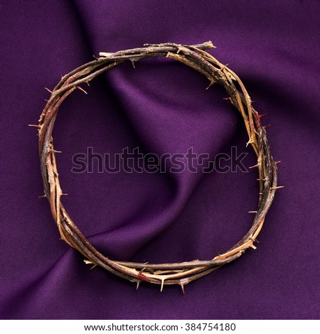 high-angle shot of a recreation of the crown of thorns of Jesus Christ on a purple drapery - stock photo