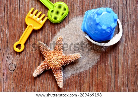 high-angle shot of a rustic wooden surface with a starfish on a pile, and some beach toys such as a shovel, a rake and a pail - stock photo