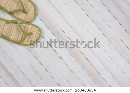 High angle shot of a single pair of summer flip flops on white wood surface. The sandals are in the upper left corner leaving room for your copy. - stock photo