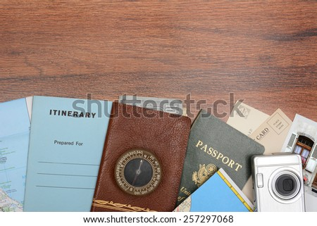 High angle shot of a travel still life. Items include: passport, wallet, post cards, camera, pictures, maps, and itinerary folder on a wood desk. Horizontal format with copy space at the top. - stock photo