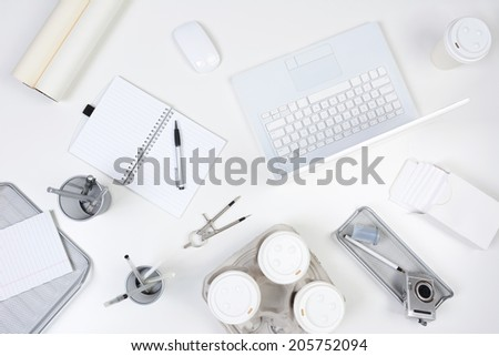 High angle shot of a white desk with primarily white and silver office objects. Items include, laptop computer, pad, pens, coffee cups, compass, camera and film. - stock photo
