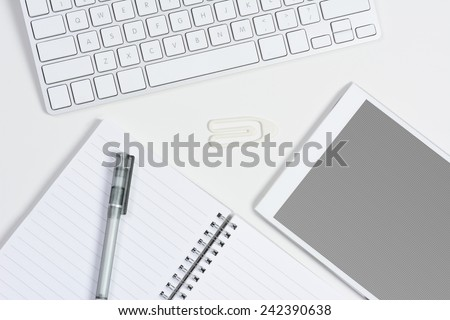 High angle shot of a white home office desk with keyboard, tablet computer with a gray grid screen, and note pad and pen. Horizontal format. - stock photo
