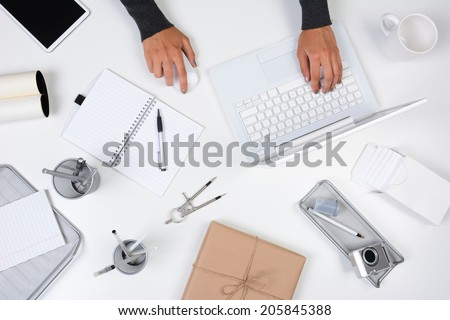High angle shot of a woman working from her home office. Only her hands are visible as she types on her laptop computer. The white desk is neat with white and silver items. - stock photo