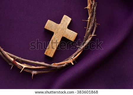 high-angle shot of a wooden christian cross and the crown of thorns of Jesus Christ on a purple drapery - stock photo