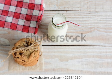 High angle shot of an after school snack of chocolate chip cookies and an old fashioned bottle of milk. The cookies are tied with twine and with a napkin on a rustic wood kitchen table. - stock photo