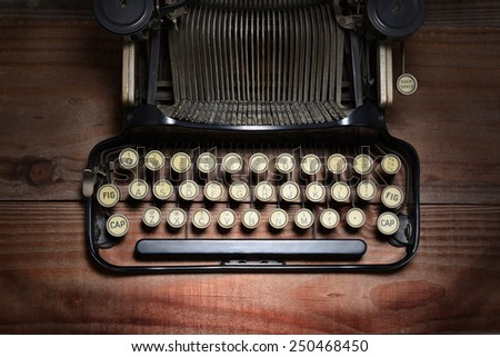 High angle shot of an antique typewriter on a rustic wood table. Closeup on the keys showing only part of the machine. Horizontal format with spot lighting.  - stock photo
