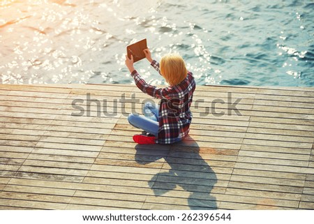 High angle shot of an attractive young woman taking a self portrait while sitting on wooden pier, cute hipster girl relaxing at her sunny holiday photographing outdoors, flare sun light - stock photo