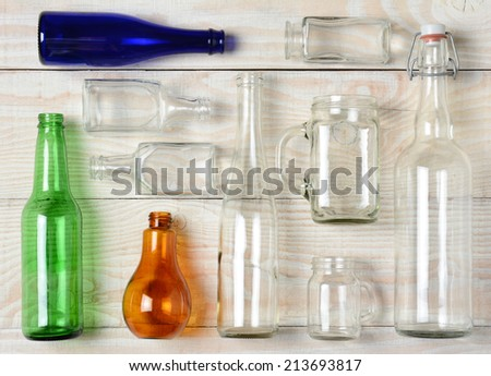 High angle shot of assorted glass bottles on a whitewashed wooden table. Clear Glass, Blue and Green and Brown Bottles and containers of various sizes and shapes. Horizontal Format.
