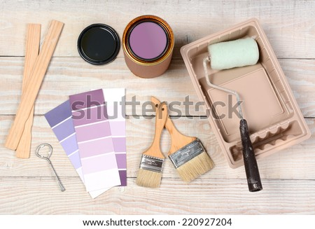 High angle shot of equipment laid out in preparation to paint. Items include: an open paint can, paint, roller, brushes, chip chart, stirrers, opener and tray.  - stock photo