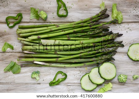 high-angle shot of some different raw green vegetables, such as green pepper, asparagus, broccoli or zucchini, on a rustic white table - stock photo