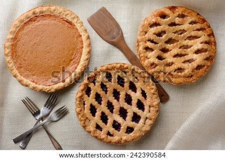 High angle shot of three fresh baked homemade pies, Apple, Cherry and Pumpkin on a burlap table cloth. Horizontal format with forks and wooden spatula. - stock photo
