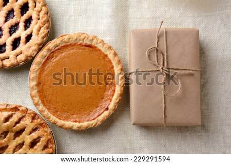 High angle shot of three holiday pies and a wrapped parcel on a burlap tablecloth. The cherry and apple pies run out of the frame with a whole pumpkin pie and package dominate the frame. - stock photo