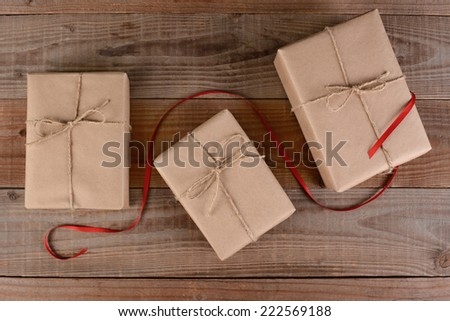 High angle shot of three plain wrapped Christmas presents. Brown paper and twine wrapped packages with a red ribbon running through the middle on rustic wood surface. - stock photo
