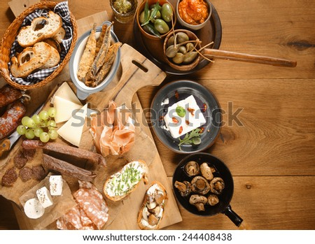 High Angle Shot of Various Freshly Made Mouth Watering Appetizers and Snacks on Wooden Board and Plates on Top of Wooden Table - stock photo