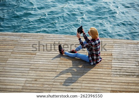 High angle shot of young tourist woman taking a photo of a beautiful view with her camera tablet, cute hipster girl relaxing at her sunny holiday photographing outdoors, young woman on sea pier - stock photo