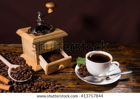 High Angle Still Life of Brewed Cup of Coffee on Rustic Wooden Table Beside Traditional Hand Grinder and Scattering of Roasted Coffee Beans with Wooden Spoon - stock photo