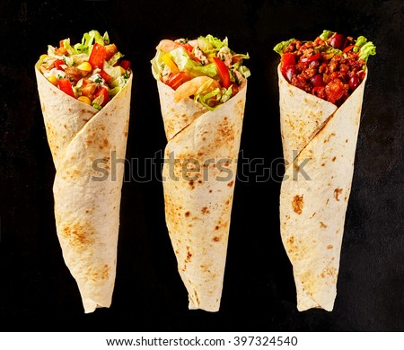 High Angle Still Life of Trio of Tex Mex Fajita Wraps on Black Background - Variety of Grilled Flour Tortilla Wraps Stuffed with Different Fillings Such as Chicken and Chili - stock photo