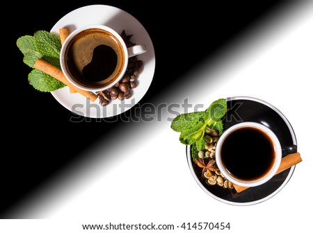 High Angle Still Life View of Black Coffee Served in Black and White Cups with Saucers Garnished with Fresh Mint, Cinnamon Sticks and Coffee Beans on Black and White Split Background with Copy Space - stock photo