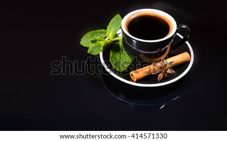 High Angle Still Life View of Black Coffee Served in Cup and Saucer with Fresh Mint Sprig, Cinnamon Stick and Star Anise on Shiny Black Counter Surface with Copy Space - stock photo