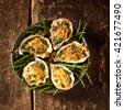 High Angle Still Life View of Five Oysters with Gourmet Gratin Cheese Topping Arranged on Plate with Green Garnish on Rustic Wooden Table - stock photo
