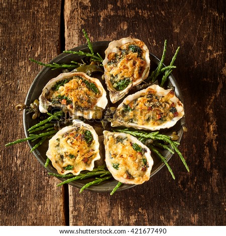 High Angle Still Life View of Five Oysters with Gourmet Gratin Cheese Topping Arranged on Plate with Green Garnish on Rustic Wooden Table