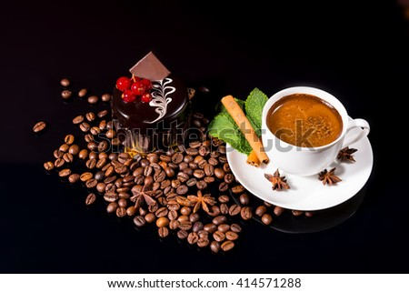 High Angle Still Life View of Frothy Gourmet Espresso Coffee Garnished with Fresh Mint Leaves, Cinnamon Stick and Star Anise Served with Individual Dark Chocolate Cake and Roasted Coffee Beans - stock photo
