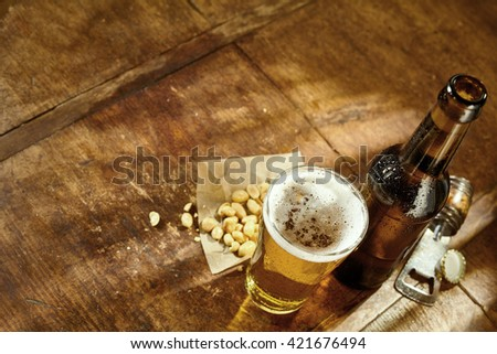 High Angle Still Life View of Glass of Cold Ale, Bottle of Beer, Bowl of Peanuts and Bottle Cap Opener on Rustic Wooden Table with Copy Space - stock photo