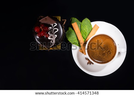 High Angle Still Life View of Gourmet Espresso Coffee Garnished with Fresh Mint Leaves, Cinnamon Stick and Star Anise Served with Dark Chocolate Individual Cake Garnished with Red Berries - stock photo