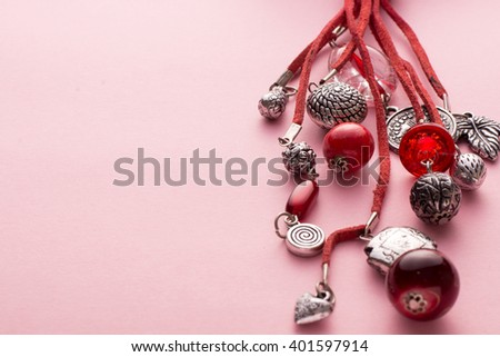 High Angle Still Life View of Handmade Artisan Jewellery on Pink Background - Stylish and Funky Necklace Made with Red Leather and Adorned with Silver Charms and Red Beads and Stones - stock photo