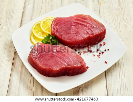 High Angle Still Life View of Two Raw Tuna Steaks on Square White Plate Garnished with Peppercorns, Fresh Green Herbs and Lemon Wedges on Painted Wooden Table - stock photo