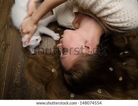High angle studio portrait of the pretty young woman lying on the floor - stock photo