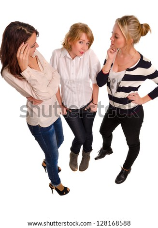 High angle studio portrait of three attractive trendy young female friends standing close together enjoying a chat isolated on white - stock photo