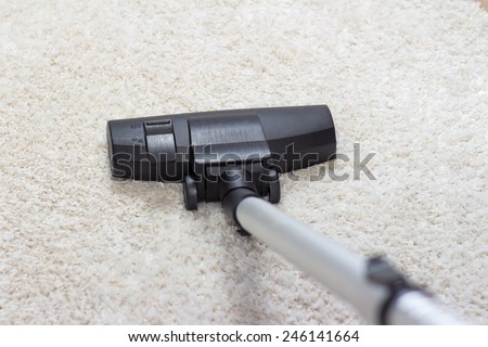 High angle view looking down the handle of a modern vacuum cleaner being used to vacuum a long pile white carpet - stock photo