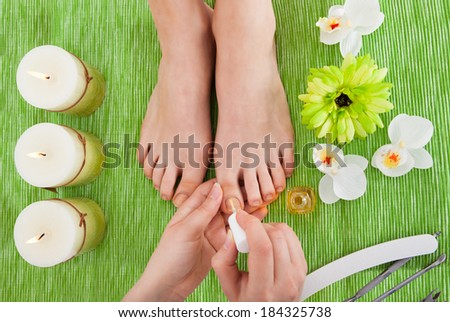 High Angle View Of A Beautician's Hand Applying Nail Varnish To Woman's Feet - stock photo