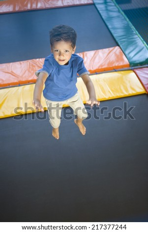 High angle view of a boy jumping on a trampoline - stock photo