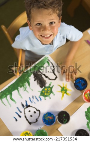 High angle view of a boy painting and smiling - stock photo