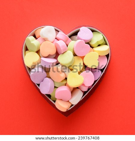 High angle view of a bunch of pastel candy hearts in a heart shaped box for Valentines Day. Square format on a red background, the candies are blank. - stock photo