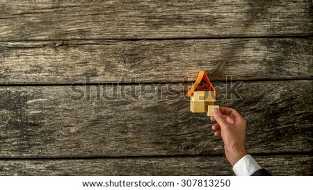 High Angle View of a Businessman Hand Assembling House Miniature on Top of a Rustic Wooden Table with Copy Space. - stock photo