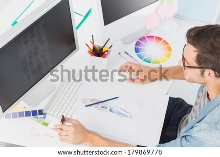 High angle view of a casual male photo editor using computer in office - stock photo